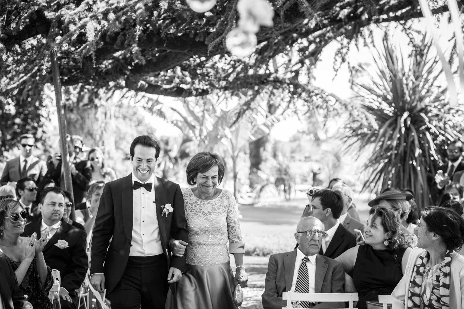 Le marié descend l'allée au bras de sa maman.