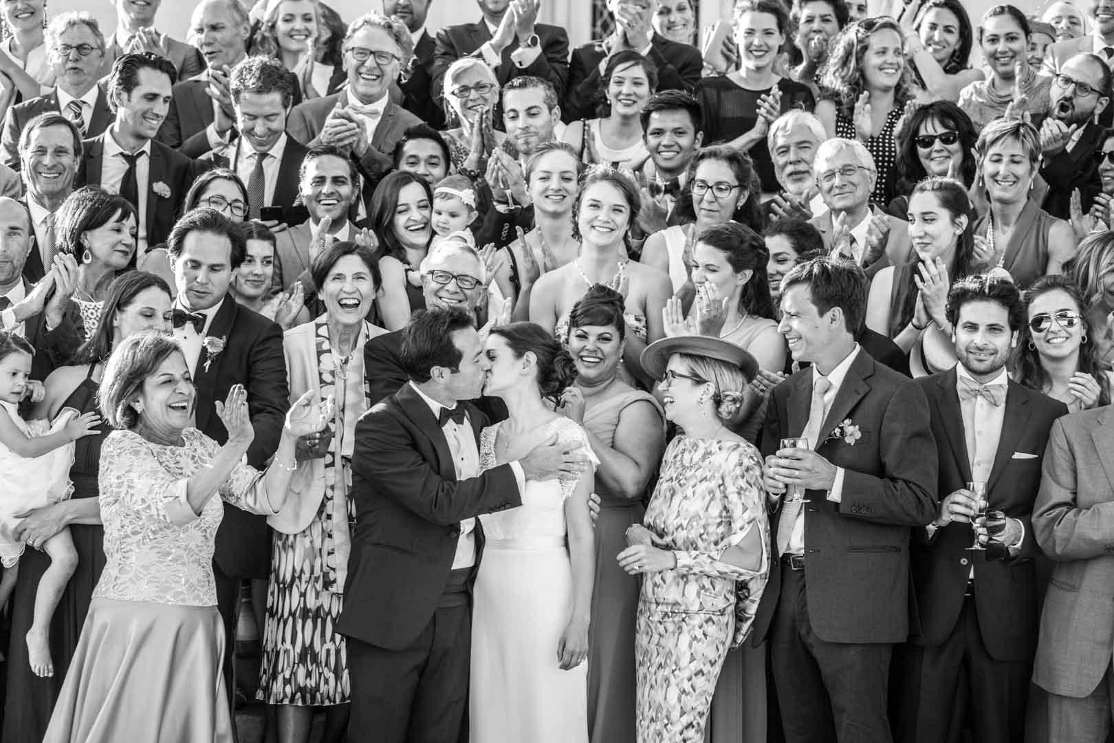 Photo de groupe, les mariés s'embrassent en premier plan. Mariage au chateau du Pape Clément à Bordeaux