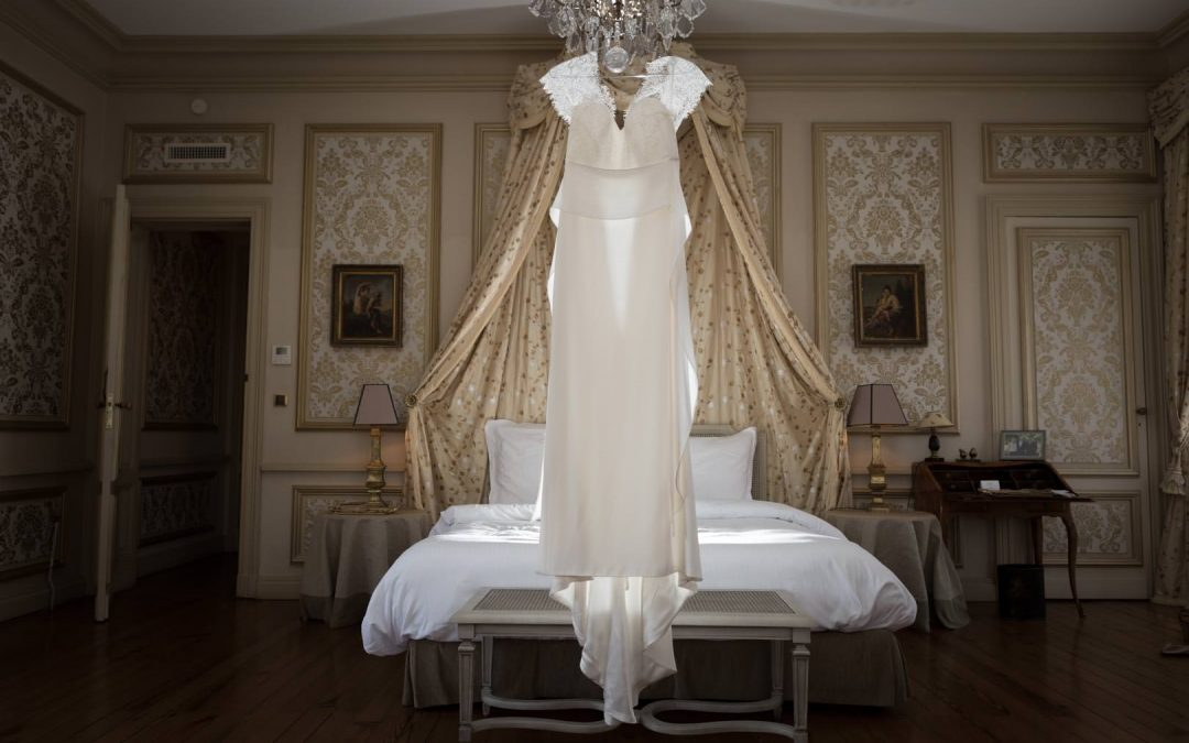 Robe de marie blanc crême suspendu à un lustre dans une chambre d'hotel luxueuse