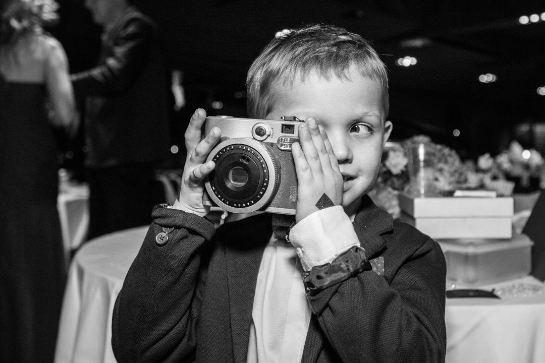 Enfant de face tenant un appareil photo, noir et blanc