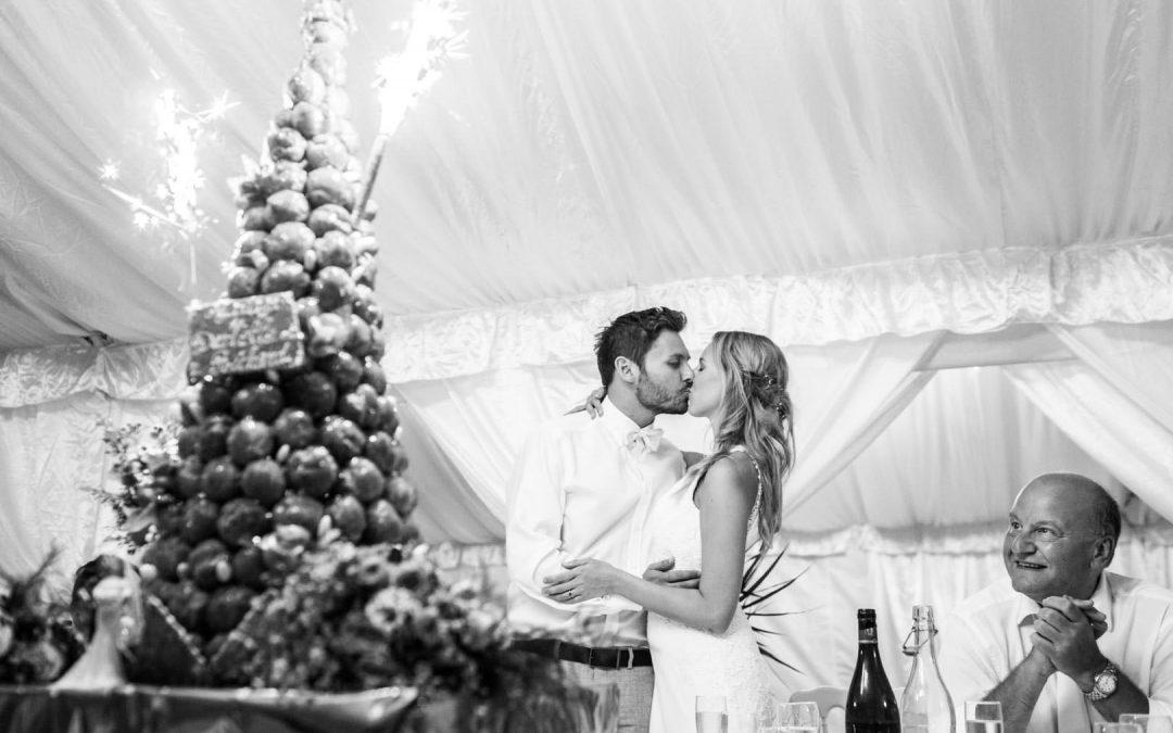 Les mariés s'embrassent devant la pièce montée