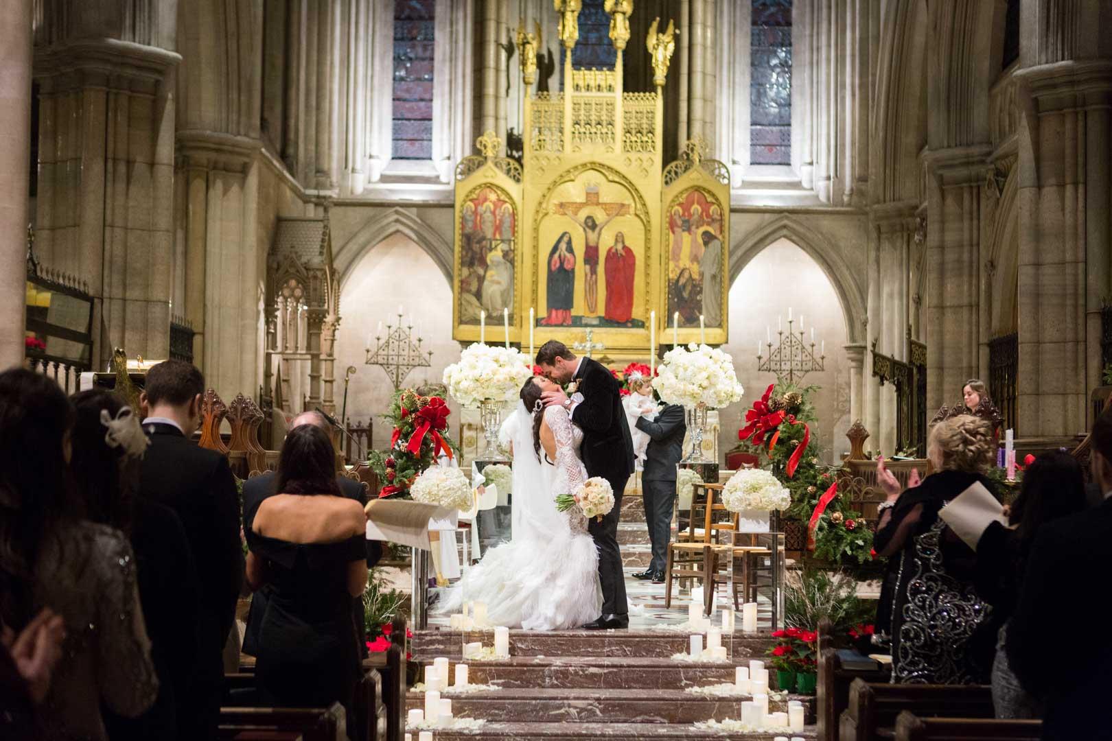 les mariés s'embrassent, au second plan, un homme à la tête de bouquet de fleur