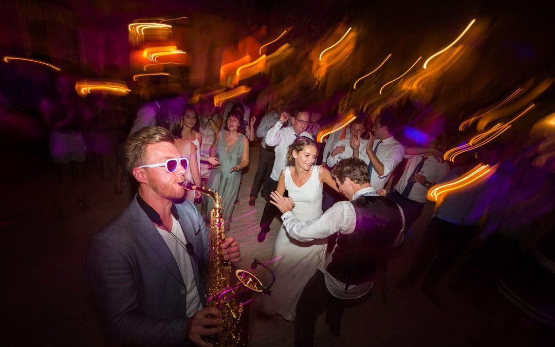 pendant la fête, on danse, on joue du saxophone avec des lunettes de soleil, à l'intérieur de nuit.