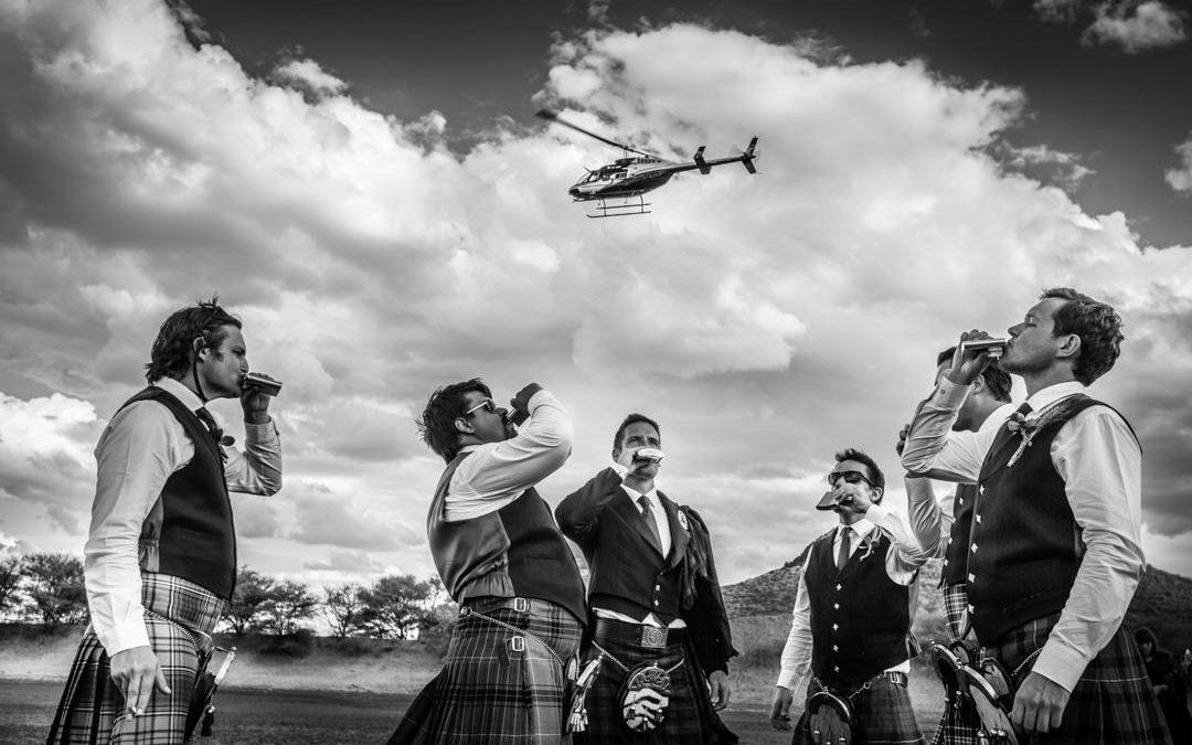 Des ecossais en kilt boivent du whisky en flasque dans la savane en Namibie, un hélicoptère vole dans le ciel.