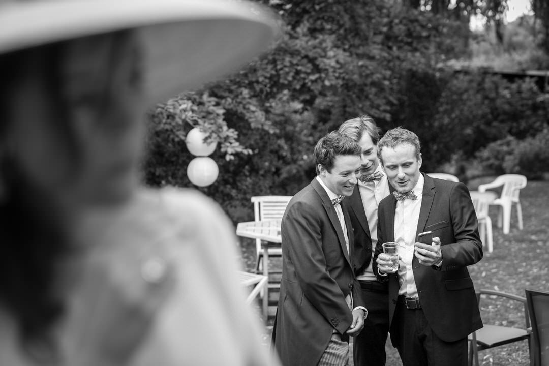 Troisi jeunes hommes sont captivé et amusé devant un smartphone