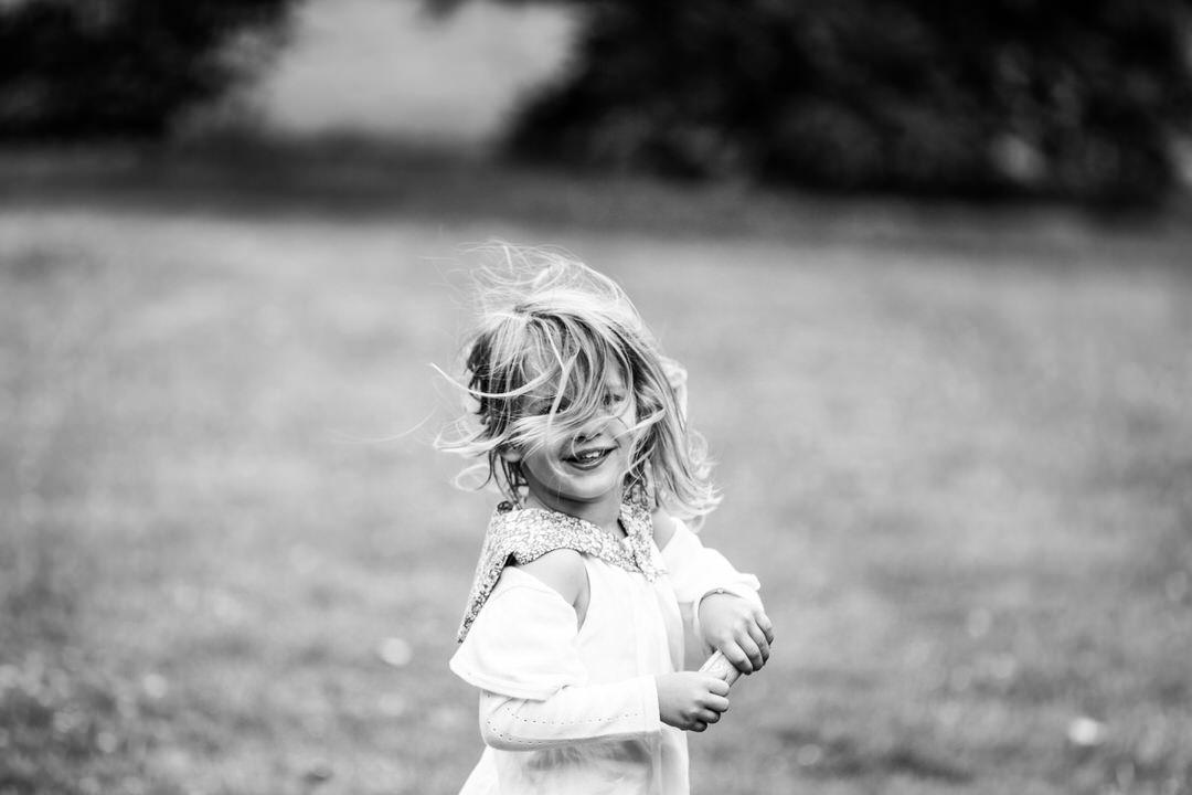 Une petite fille, cheveux au vent, tout sourire dehors. Photo noir et blanc