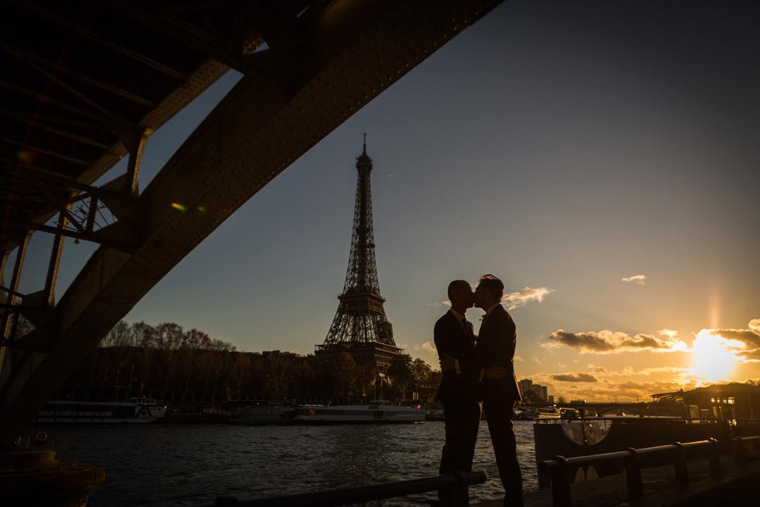 Les mariés s'embrassent devant la tour eiffel et le soleil couchant