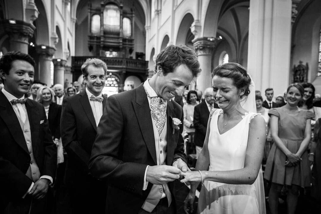 Cérémonie de mariage, le marié passe la bague au doigt de sa femme.