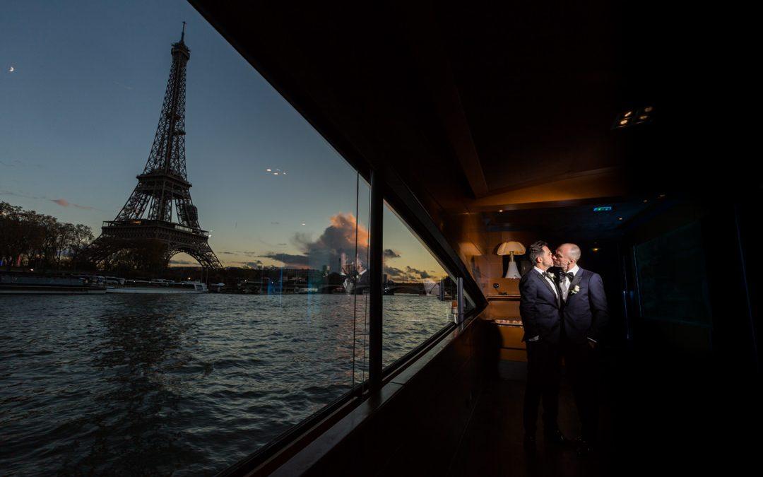 les mariés s'embrassent dans la lumière tamisé de fin de journée, dans un bateau sur la seine, à hauteur de la tour eiffel