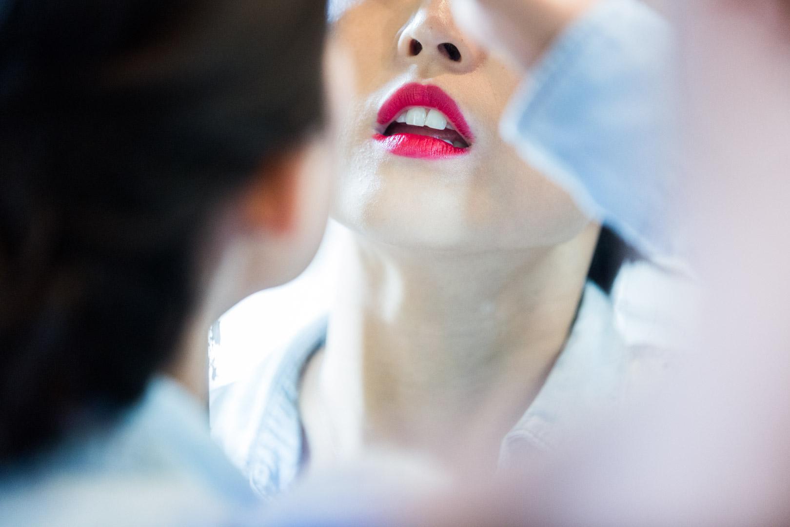 Plan serré, la mariée se maquillent, on aperçoit ses lèvres rouge carmin