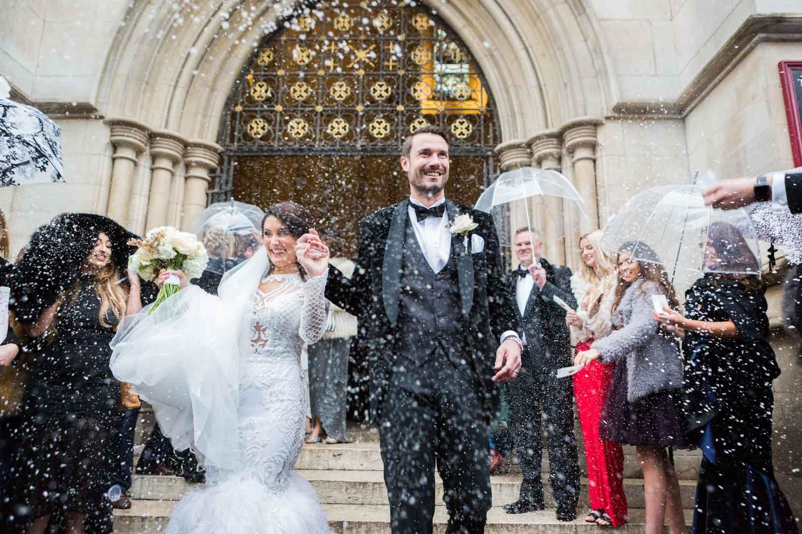 le couple sort de l'église sous les pétales de fleurs
