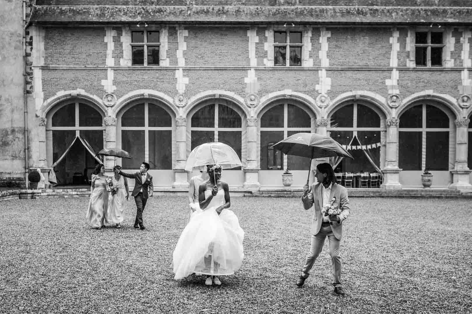 Sortie du château de la verrerie, la marié se protège de l'eau sous un parapluie transparent