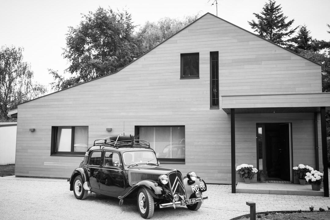 Une voiture vintage citroën, garé devant une maison moderne. Sur le pas de la porte, 3 pot en fleurs