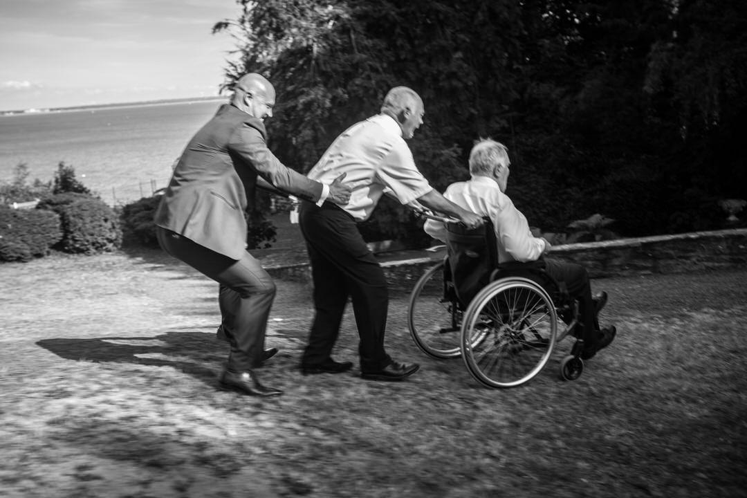 3 hommes font la chenille. Celui en tête est en fauteuil roulant.