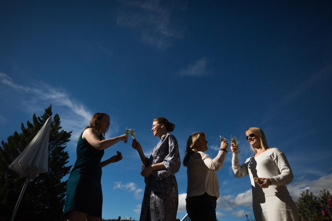4 femmes trinquent gaiement, extérieur jour.