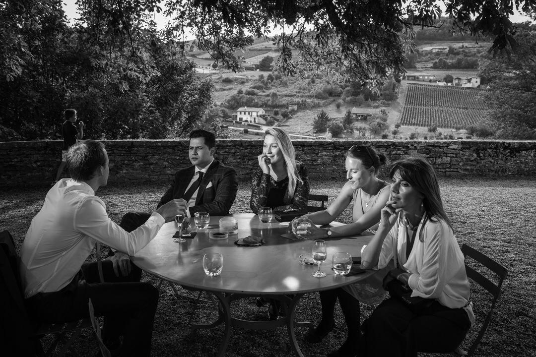 un groupe de jeunes gens, assis à une table en extérieur, derrière eux, un muret de pierre et les vignes qui déroulent le paysage