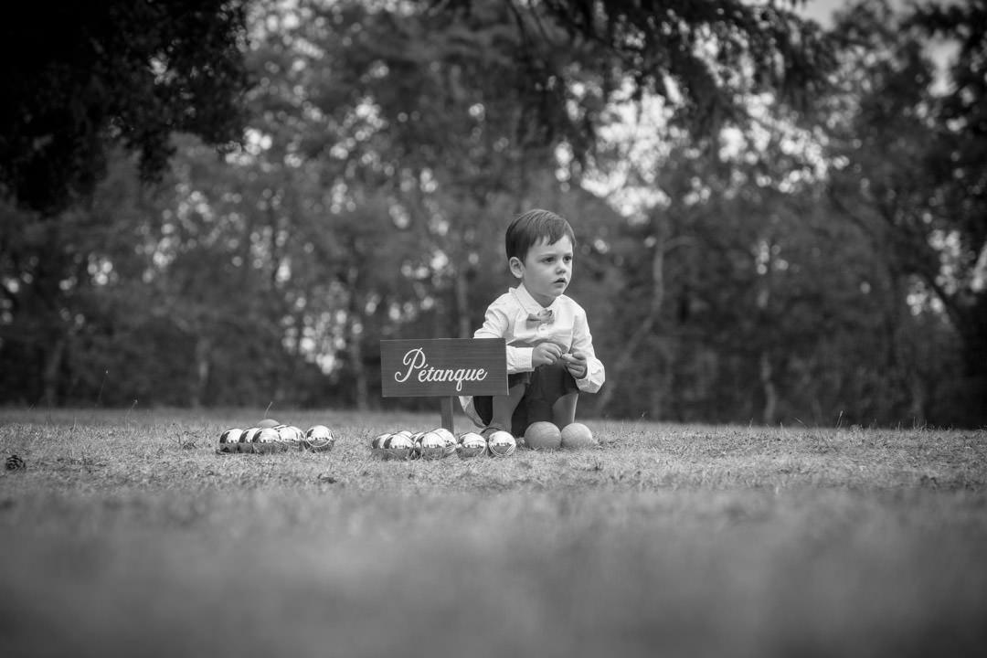 Un jeune garçon campe ses positions sur le terrain de pétanque