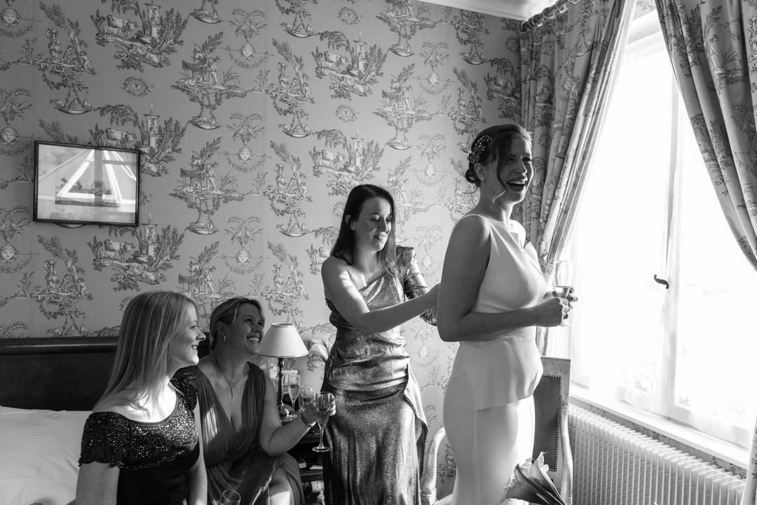 la mariée finit de se préparer et ajuste sa robe