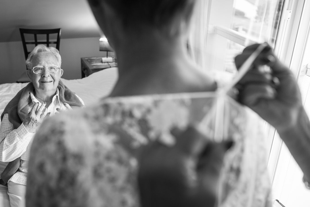 La marié de dos, flouté, on lui noue le haut de sa robe de mariage. Devant elle, assise sur un lit, sa mère la regarde avec emerveillement