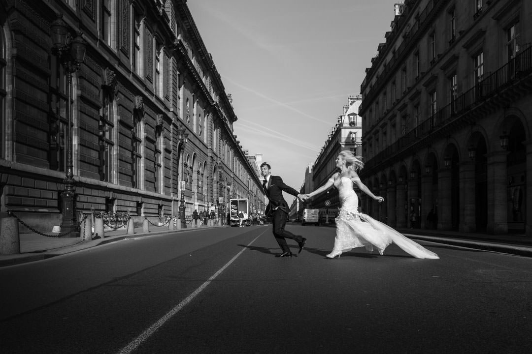 Un couple marié traversent la rue de Rivoli en courant ( Paris)
