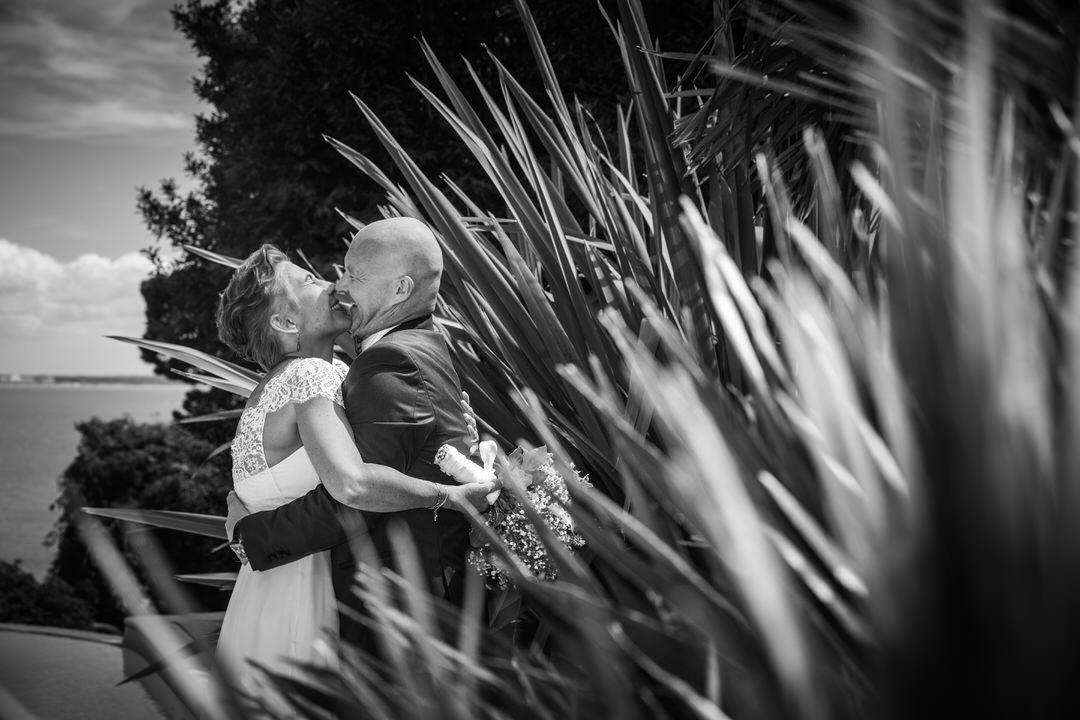 sur la côte Atlantique, le couple s'enlace en riant. On les voit de profil au travers de végétaux lisses et pointus