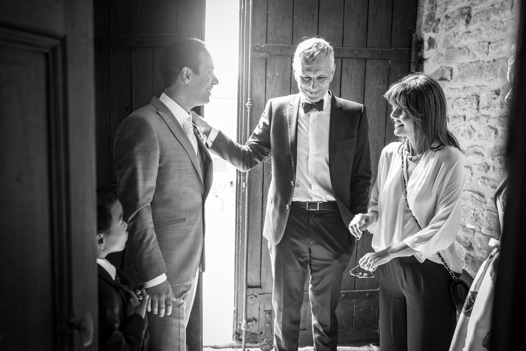 Devant une porte cochère, le marié est au côté des parents de sa futur femme.