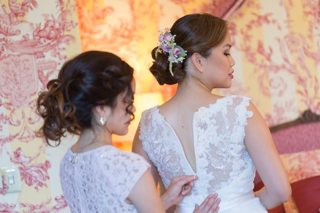 La mariée et sa demoiselle d'honneur, ajustent la robe de mariage